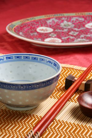 Close-up view of asian tableware (bowl, sauce cup, chopsticks and napkin) on a bamboo tablemat