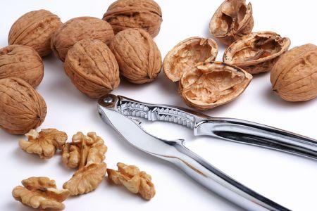 Walnuts and a nutcracker on a white background photo