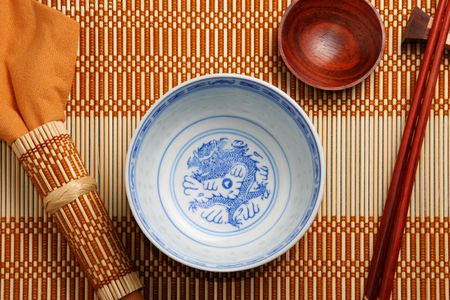 Top view of asian tableware (bowl, sauce cup, chopsticks and napkin) on a bamboo tablemat