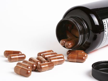 dietary supplements: Dietary supplements flowing from a container Stock Photo