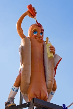street vendor: A giant cartoony hot-dog sign on the roof of a fast food shop