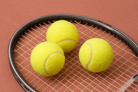 Three tennis balls on a racket head Stock Photo