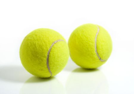 Yellow tennis balls isolated on a white background, with reflection