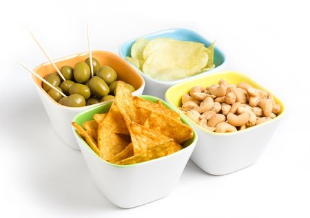 toothpick: Four cups of appetizers : olives, cashew nuts, potato chips and tortilla chips