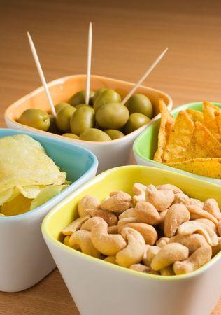 anacardo: Cuatro tazas de aperitivos: aceitunas, nueces de anacardo, papas fritas y chips de tortilla
