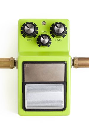 amplification: A distortion guitar effects pedal with input and output plugs isolated on a white background