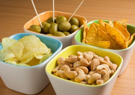 Four cups of appetizers : olives, cashew nuts, potato chips and tortilla chips