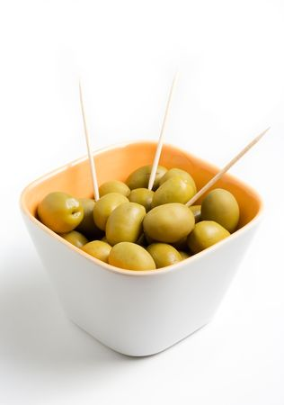 A cup of green olives isolated on a white background