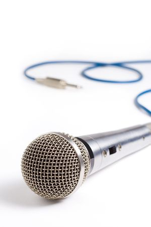 A recording studio microphone with its cord and plug out of focus photo