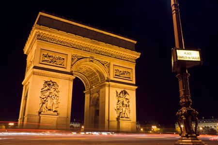 The Arc de Triomphe at night with a street plate in the foreground - Charles de Gaulle square,  Paris, France