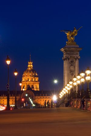 invalides: The Alexander III bridge and the dome of the Invalides at night - Paris, France Stock Photo