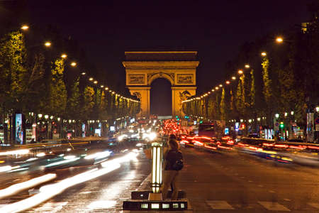Night view of the Champs-Elysees avenue leading to the Arc de Triomphe - Paris, France