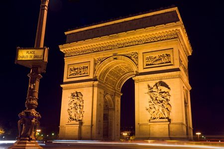 triomphe: The Arc de Triomphe at night with a street plate in the foreground - Charles de Gaulle square,  Paris, France