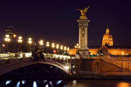 The Alexander III bridge and the dome of the Invalides at night - Paris, France Stock Photo