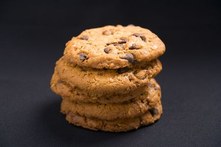 A stack of hazelnut and chocolate chips cookies on a dark background Stock Photo