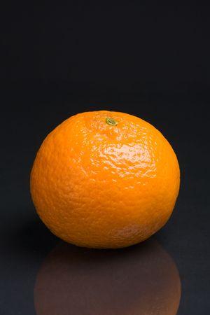 A single tangerine on a dark reflective background Stock Photo - 660153