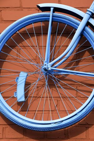 Front Wheel of Antique Bicycle painted blue against rust colored brick wall photo
