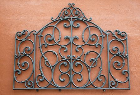A Decorative Piece of Wrought Iron Mounted to a Bright Colored Stucco Wall Stock Photo - 3337258