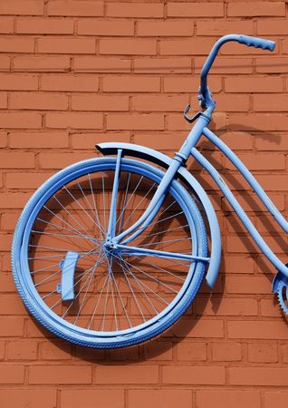 Antique Girls Bicycle Painted Blue against Rust Colored Brick Wall photo