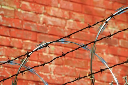 Security Fence with Razor and Barb Wire against a Brick Wall Stock Photo - 4293251