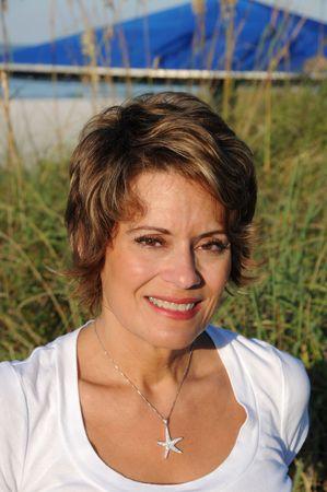 donne mature sexy: Donna attraente, godersi il sole di mattina presto in spiaggia Archivio Fotografico