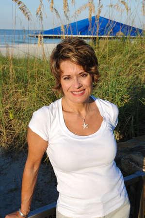 donne mature sexy: Donna attraente per godersi il sole di mattina presto in spiaggia