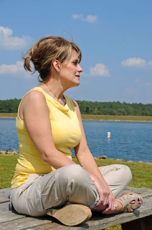 Attractive Mature Woman sitting on a Picnic Table by the Lake Stock Photo - 7872964