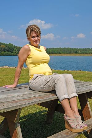 fifty: Attractive Woman sitting on picnic table by the Lake Stock Photo