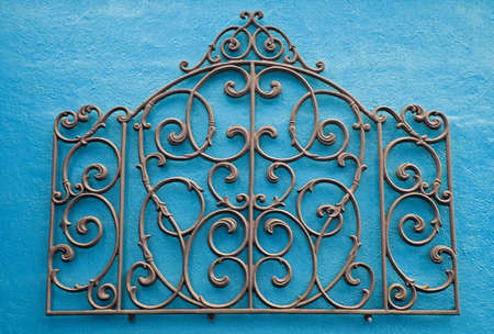 iron works: Decorative Piece of Wrought Iron Mounted to a Bright Colored Stucco Wall