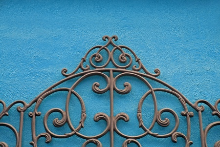 ironworks: Decorative Piece of Wrought Iron Mounted to a Bright Colored Stucco Wall                                     Stock Photo
