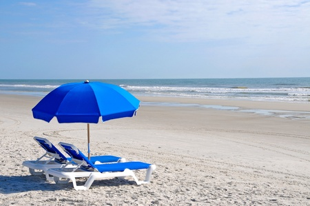 Two Beach Chairs with Blue Umbrella on the Beach photo