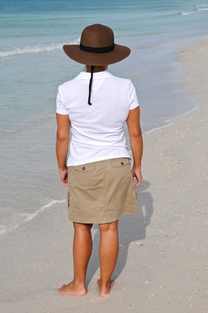 40 50: Attractive Woman Wearing a Sun Hat Standing on the Beach
