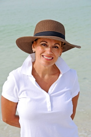Attractive Woman Wearing a Sun Hat Standing on the Beach photo