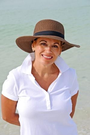donne mature sexy: Donna attraente, il portare, Standing Hat sole sulla spiaggia Archivio Fotografico