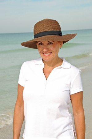 sexy mature women: Attractive Woman Wearing a Sun Hat Standing on the Beach