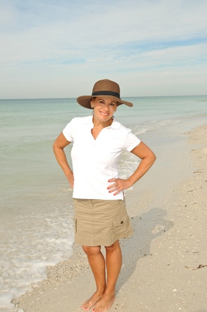 40 50: Attractive Woman Standing on the Beach Stock Photo