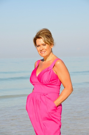 40 50: Attractive Woman Wearing A Pink Summer Dress on the Beach
