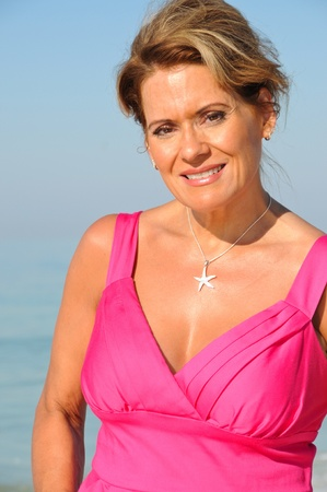 woman beach dress: Attractive Woman Wearing A Pink Summer Dress on the Beach