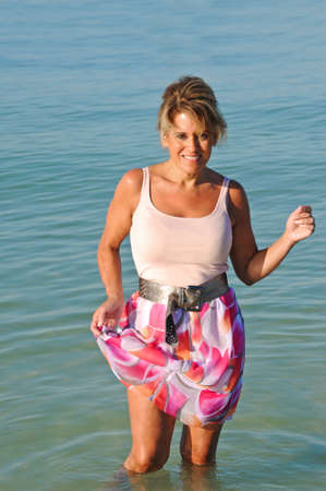 age forty: Attractive Woman Standing in the Ocean Surf