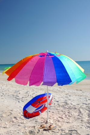 umbella: Colorful Umbrella and Float on the Beach Stock Photo