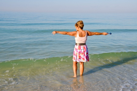 Attractive Woman Standing in the Ocean Holding Her Arms Out photo