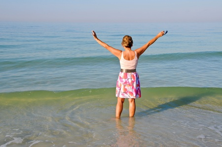Attractive Woman Standing in the Ocean With Her Arms Held Up photo