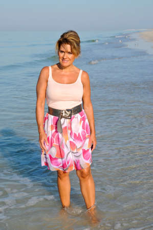 fifty: Attractive Woman Walking on the Beach in a Summer Dress Stock Photo