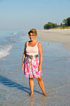 donne mature sexy: Donna attraente Camminando sulla spiaggia in un abito estivo Archivio Fotografico