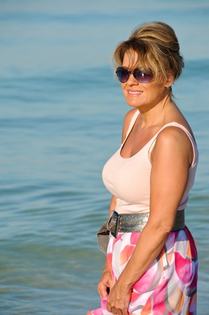 Attractive Woman Walking on the Beach in a Summer Dress photo