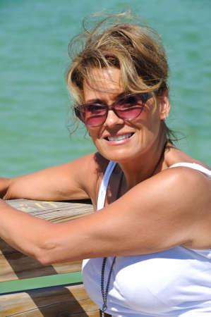 donne mature sexy: Donna attraente che si siede su un Boardwalk in spiaggia Archivio Fotografico