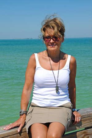 mujeres maduras: Atractiva mujer sentada en un paseo mar�timo en la playa Foto de archivo