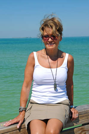 Attractive Woman Sitting on a Boardwalk at the Beach  Reklamní fotografie