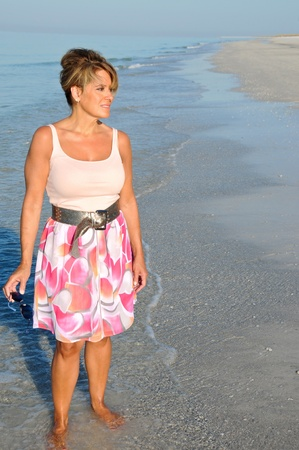 40 50: Attractive Woman Walking on the Beach in a Summer Dress Stock Photo