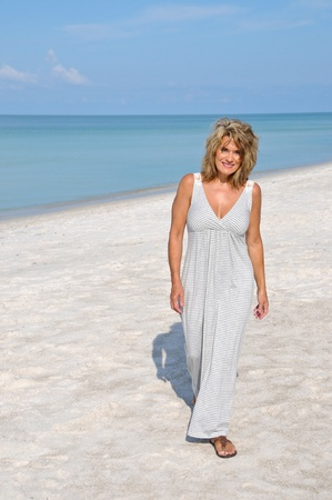 Attractive Woman Walking on the Beach in a Sundress photo